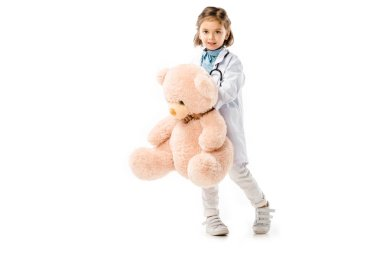 Kid dressed in doctors white coat with stethoscope holding big teddy bear isolated on white stock vector