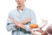 Fotografie oříznutý obraz člověka, nejevící žádné známky ženě navrhuje burger izolované na bílém