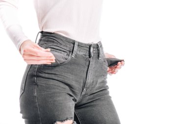 cropped image of girl showing empty jeans pockets isolated on white