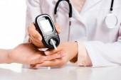 oříznutý obraz lékaře měření pacienta hladinu glukózy v krvi se glukometr izolované na bílém, cukrovka koncepce