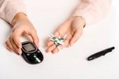 oříznutý obraz ženy držící glukometr a proužky izolované na bílém, cukrovka koncepce