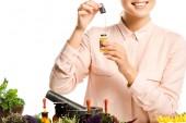 oříznutí obrázku usmívající se žena držící kapátkem a skleněná láhev s esenciálním olejem izolované na bílém