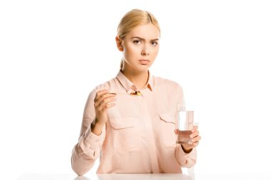 irritated attractive woman holding spoon of pills and glass of water isolated on white