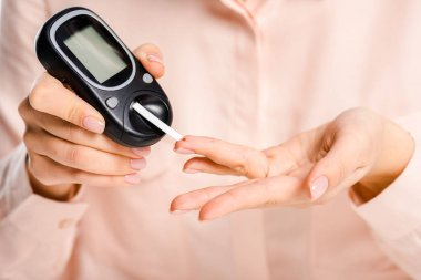 cropped image of woman measuring level of glucose in blood with glucometer isolated on white, diabetes concept