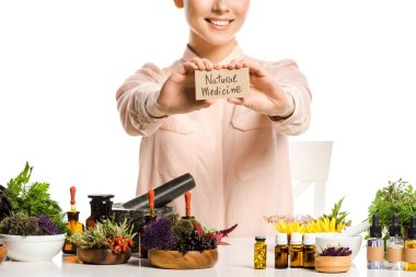 cropped image of woman showing card with natural medicine sign isolated on white