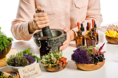 cropped image of woman preparing natural medicines with mortar and pestle isolated on white