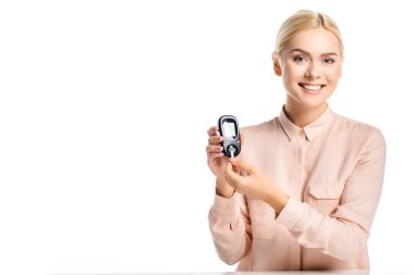 smiling woman putting strip into glucometer isolated on white, diabetes concept