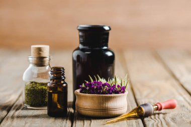 glass bottles of essential oils and flowers on wooden tabletop, alternative medicine concept