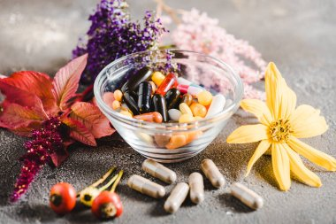 pharmacological pills in glass bowl and colored flowers on wooden tabletop, alternative medicine concept