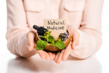 cropped image of woman holding bowl with essential oil and natural medicine sign isolated on white