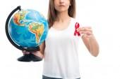 Fotografie oříznutí obrazu ženy držící glóbus a červenou stužkou izolované na bílém, svět pomáhá den koncept