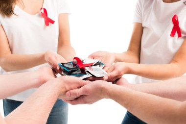 cropped image of men and women holding condoms and red ribbon isolated on white, world aids day concept