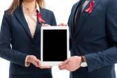 Oříznout obrázek podnikatelé s červené pásky na držení tabletu s prázdnou obrazovkou izolované na bílém obleky, svět pomáhá den koncept