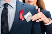 Fotografie cropped image of businesswoman giving condom to businessman with red ribbon on suit isolated on white, world aids day concept