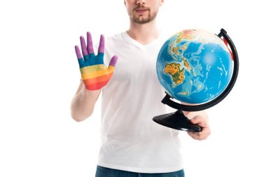 cropped image of man holding globe and showing hand painted in rainbow isolated on white, world aids day concept