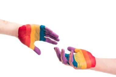 cropped image of gay couple reaching hands painted in colors of pride flag isolated on white, world aids day concept