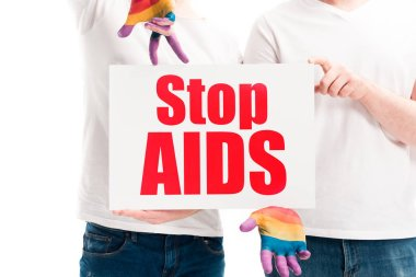 cropped image of gay couple holding card with stop aids text isolated on white, world aids day concept