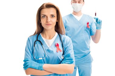 doctors standing with red ribbons and syringe, looking at camera isolated on white, world aids day concept