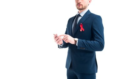 Cropped image of businessman with red ribbon on suit using smartphone isolated on white, world aids day concept stock vector