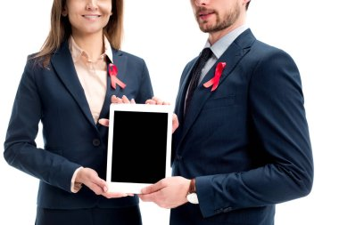 cropped image of businesspeople with red ribbons on suits holding tablet with blank screen isolated on white, world aids day concept