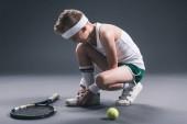 nedospělý chlapec v oblečení s tenisovou raketu a míček na tmavém pozadí