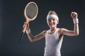 portrét happy boy v oblečení s tenisovou raketu na tmavém pozadí