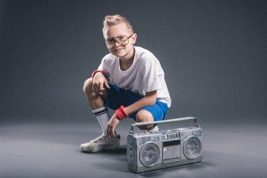 stylish preteen boy in eyeglasses with boombox posing on grey backdrop
