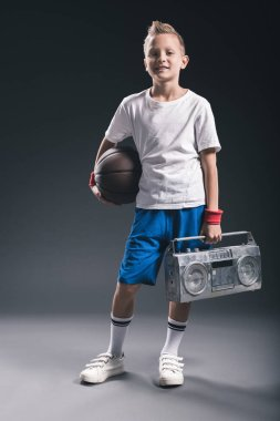 stylish boy with basketball ball and boombox on grey backdrop