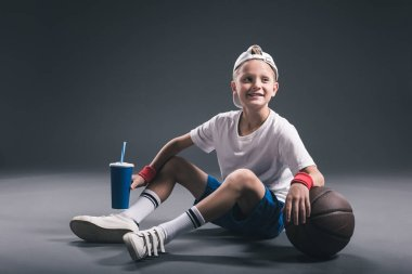 smiling preteen boy with soda drink and basketball ball on grey backdrop