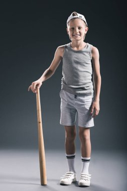 smiling boy in sportswear with baseball bat on grey backdrop