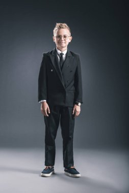 pre-adolescent boy dressed as businessman in eyeglasses looking at camera on dark background