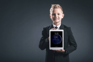 portrait of smiling boy dressed like businessman showing tablet in hands on grey backdrop