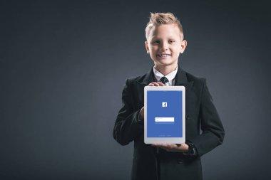 portrait of smiling boy dressed like businessman showing tablet with facebook logo in hands on grey backdrop