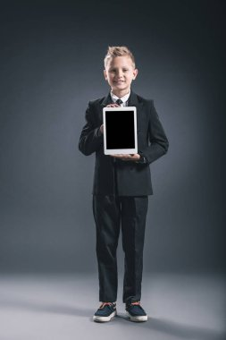smiling boy dressed like businessman showing tablet with blank screen in hands on grey backdrop
