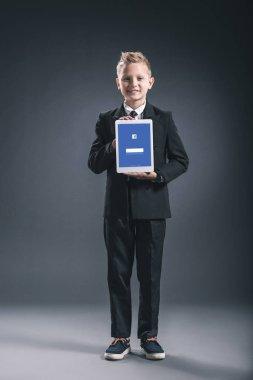 smiling boy dressed like businessman showing tablet with facebook logo in hands on grey backdrop
