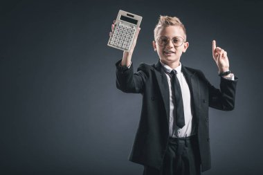 portrait of boy dressed as businessman in eyeglasses gesturing and showing calculator on dark background