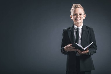 smiling boy in businessman suit and eyeglasses with notebook on grey backdrop