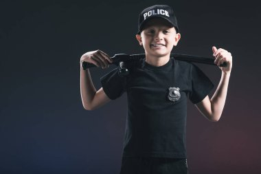 portrait of smiling preteen boy in policeman uniform with truncheon on dark backdrop