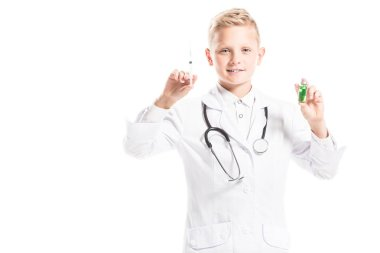portrait of preteen boy in doctors white coat with stethoscope, medicine and syringe isolated on white