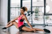 krásná africká americká sportovkyně, táhnoucí se na podlahu v tělocvičně