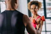 Photo partial view of african american male trainer helping sportswoman to exercising with dumbbell at gym