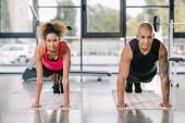 šťastný mladý americký pár sportovců dělá prkno na fitness rohože v tělocvičně