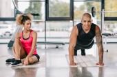 pohledný americký sportovec dělá prkno, zatímco jeho přítelkyně sedí poblíž v tělocvičně