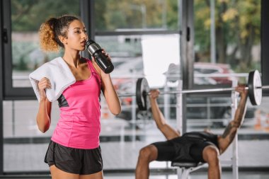 attractive african american sportswoman drinking water from sport bottle while her boyfriend exercising behind at gym