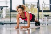 Fotografie glücklich afroamerikanische Sportlerin Plank auf Fitness-Matte im Fitnessstudio zu tun