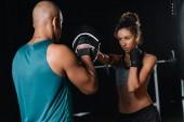Fotografie Heckansicht des muskulösen männlichen Trainer Training mit Boxerin in Turnhalle