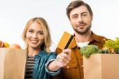 Selektivní fokus žena zobrazeno kreditní karty při její přítel stál s nákupní tašky plné výrobků izolované na bílém