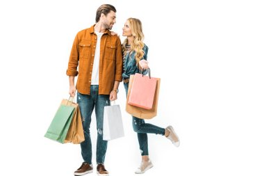 couple holding colorful shopping bags and looking at each other isolated on white