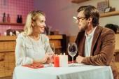 šťastný mladý pár, drželi se za ruce a mají datum u stolu v restauraci