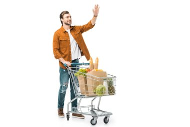 Smiling man waving by hand and standing near shopping trolley with products in paper bags isolated on white stock vector